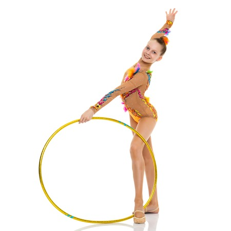 A girl gymnast performs an exercise with a hoop. Stock Photo