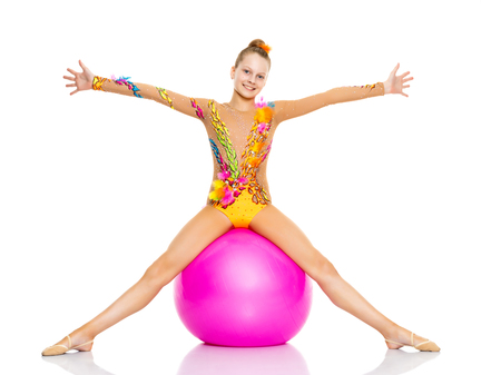 little girl doing exercises on a big ball for fitness. Banque d'images