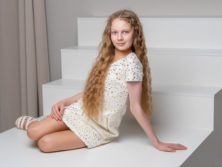 Beautiful little girl is sitting on the white staircase. Stok Fotoğraf