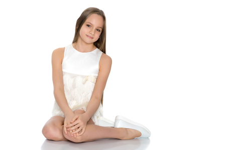 A teenage girl is sitting on the floor. Stockfoto