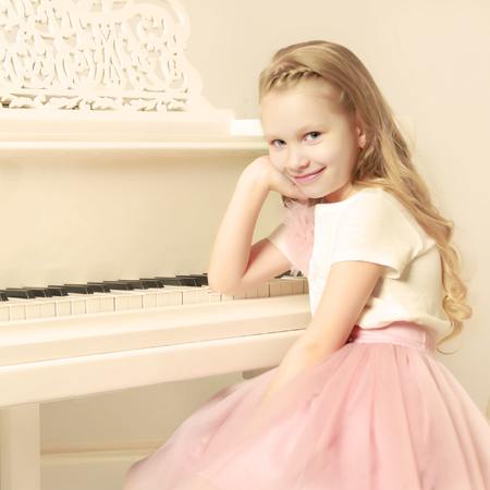 A little girl is sitting at the white piano.