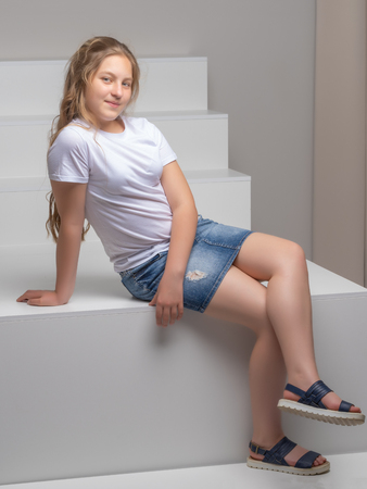 A teenage girl is sitting on a white staircase.