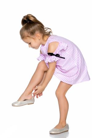 La niña se pone los zapatos.