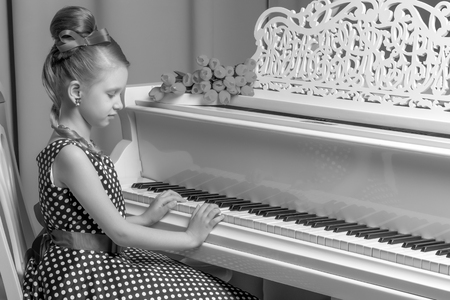 Little girl plays the piano, black and white photo.