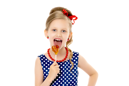 A little girl licks lollipop.