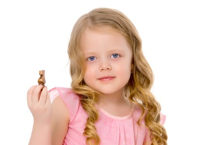 The little girl holds a chess piece in her hand. Stock Photo