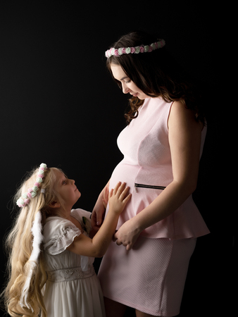 The girl in the image of an angel hugs the tummy of her eldest p