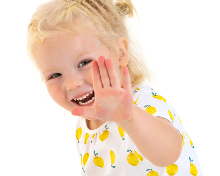 A happy little girl is waving her hand. Stock Photo