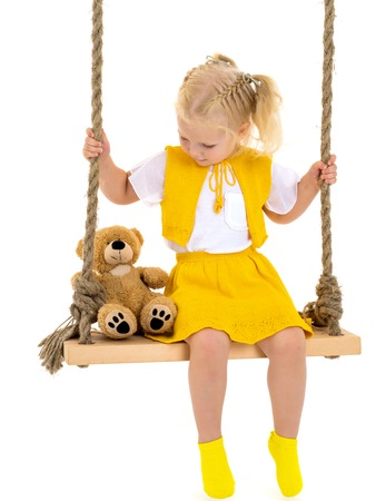 A little girl is swinging on a swing with a teddy bear.