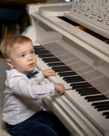 A little boy is playing the piano.