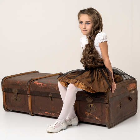 A little girl is sitting on a wooden box. Banco de Imagens