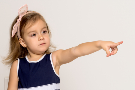 Little girl points with a finger Imagens