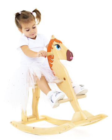 Girl swinging on a wooden horse.