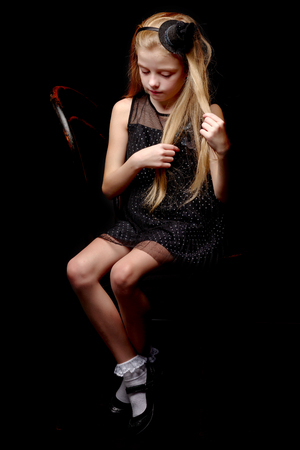 Little girl straightens her hair in the studio on a black backgr Imagens