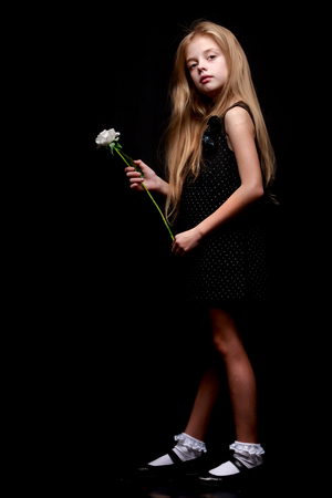 Little girl with a white flower on a black background. Foto de archivo