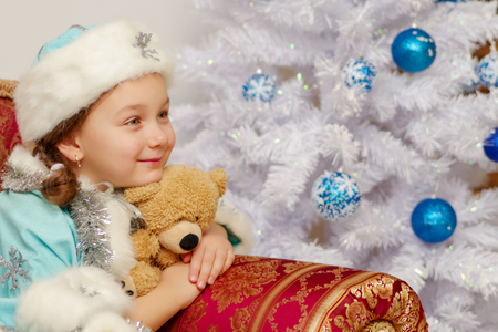Little girl in the snow maiden costume with a teddy bear near th Stock Photo