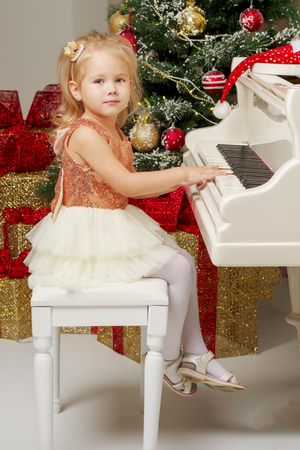 Little girl near the piano and Christmas tree.
