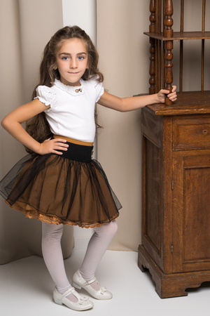 Little girl in the room with retro furniture of the last century