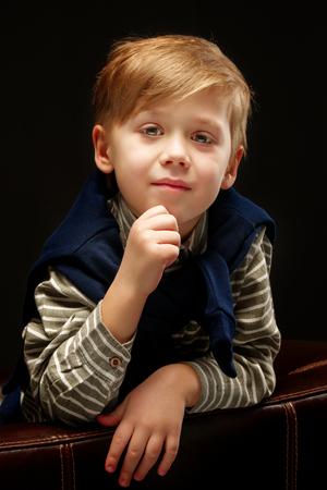 Beautiful little boy on a black background, close-up. Stock Photo