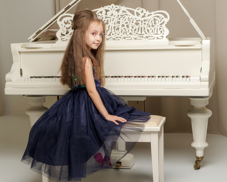 The girl is at the white grand piano.