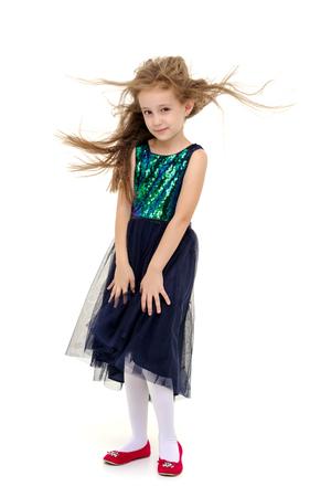 Little girl in a dress developing in the wind.