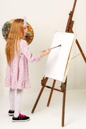 Little girl with a palette and brush near the easel. Imagens