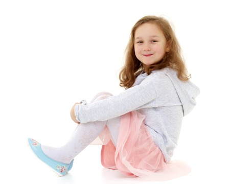 Little girl hugging her knees. Фото со стока