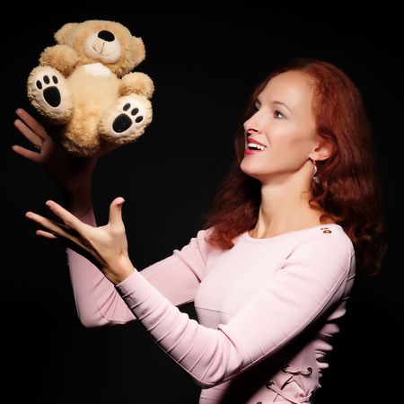 Red-haired girl model posing with a teddy bear. On a black backg