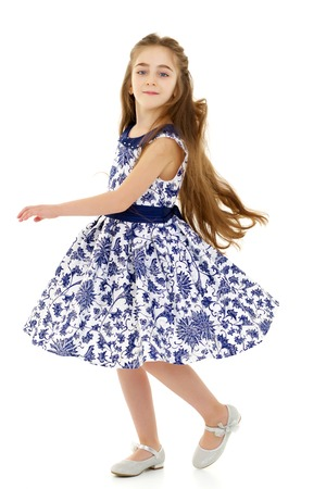 A little girl in a dress is spinning. Banco de Imagens