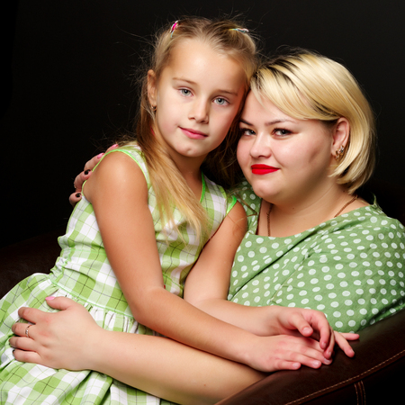 Mom and daughter are hugging on a black background. Stock Photo