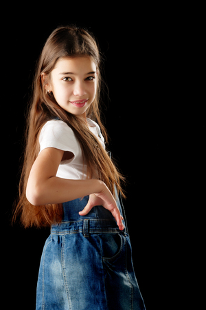 Little girl in denim clothes on a black background.
