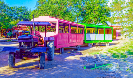 Tourist train from multi-colored cars attached to the tractor. Фото со стока - 120796317