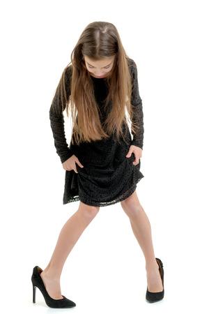 Niña con zapatos de gran tamaño. Foto de archivo