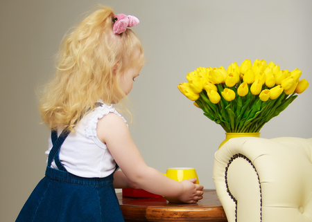 A little girl drinks water from a big yellow mug. Stock Photo