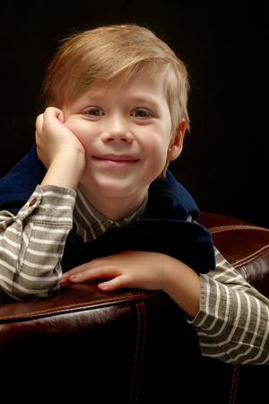 Beautiful little boy on a black background, close-up. 스톡 콘텐츠