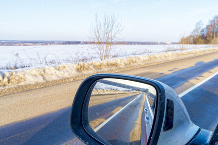 View of the asphalt road through the car mirror. Imagens