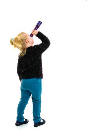 Una niña mira por un telescopio o un caleidoscopio.