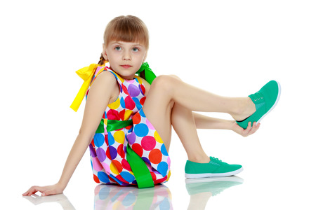 A little girl in a dress with a pattern from multi-colored circl