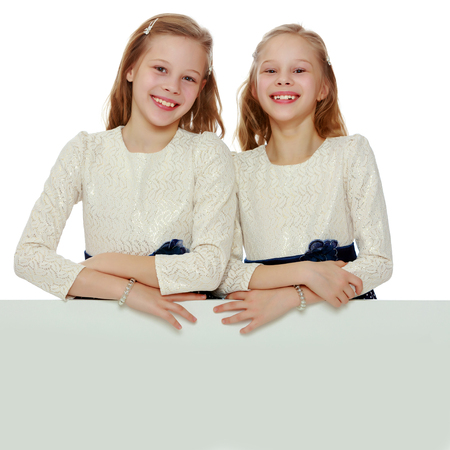 Two little girls peeking out from behind a white advertising ban