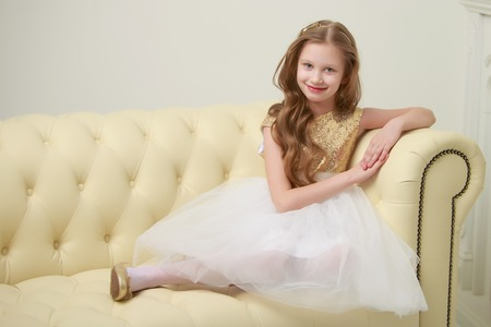 Little girl is sitting on the couch