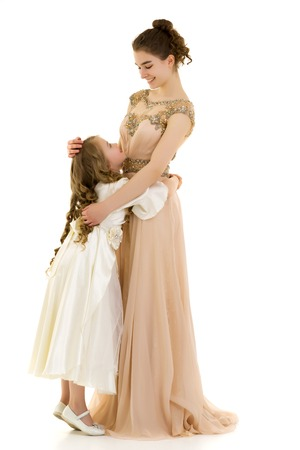 A young girl hugs her little sister.