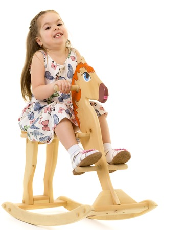 Girl swinging on a wooden horse. Stock Photo - 123310937