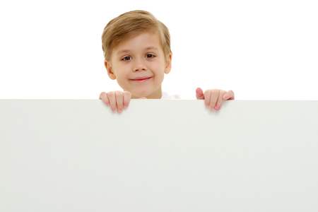 A little boy is looking from behind an empty banner.