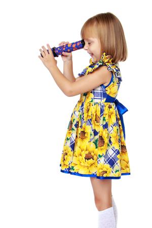 Una niña mira por un telescopio o un caleidoscopio. Foto de archivo