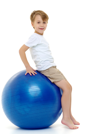 The little boy on the big ball is engaged in fitness. White T-sh