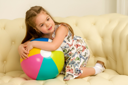 Little girl with a ball on the couch.