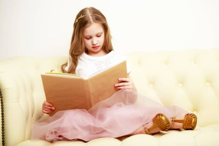 A little girl is sitting on the couch and reading a book.