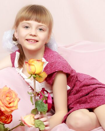 Little girl with a bouquet of tea roses. Stock Photo - 124756815