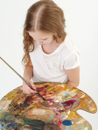 Little girl with palette and brush learning to draw.