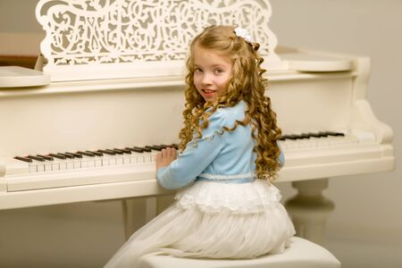Beautiful little girl is playing on a white grand piano.
